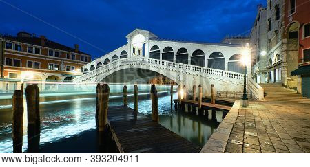 Illuminated Rialto Bridge On The Grand Canal In Venice, Italy In The Evening.