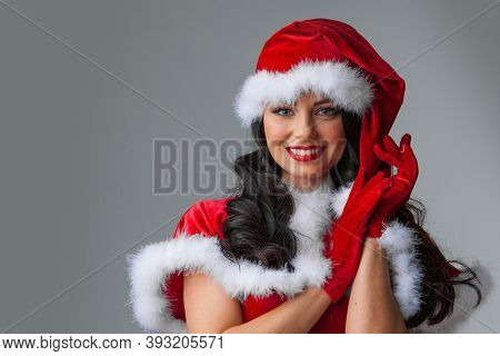 Young happy smile woman wear Santa Clause costume, attractive christmas new year party girl looking at camera, gray background