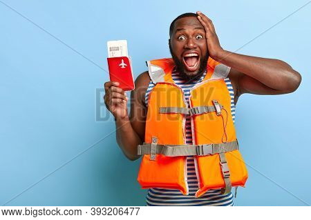 Photo Of Overjoyed Black Man Rejoices Summer Rest, Holds Passport With Tickets, Has Pleased Facial E