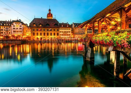 Lucerne Flowery Chapel Bridge At Night Reflected On River. Amazing Nightlife Of Lucerne City Illumin
