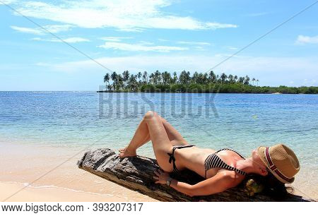 Young Beautiful Woman Enjoying Her Time And Resting Close To The Sea In The Southern Beach Of \