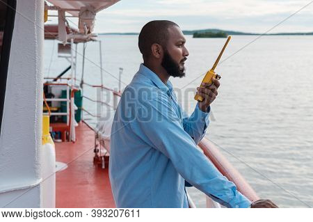 Deck Officer On The Deck Of A Ship Or Offshore Vessel. You Have In Your Hands A Vhf Walkie-talkie Ra