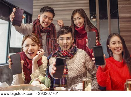 Young People Showing The Mobile Phone To Camera In The Restaurant
