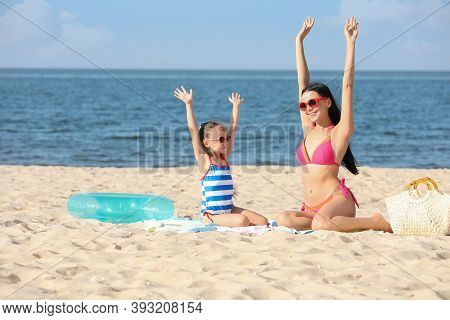 Happy Mother And Daughter On Sandy Beach Near Sea. Summer Holidays With Family