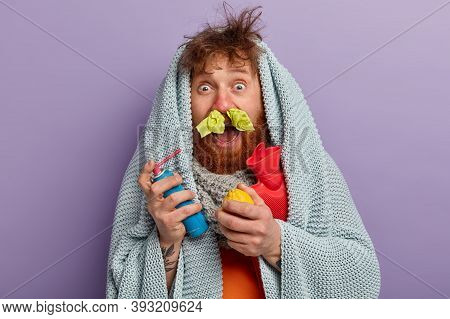 Unhappy Frustrated Shocked Man Holds Spray, Lemon And Hot Water Bottle, Wrapped In Coverlet, Has All