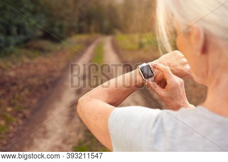 Close Up Of Senior Woman Running In Countryside Exercising Checking Smart Watch Fitness Activity App