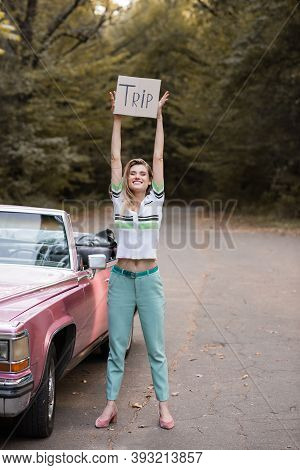 Young Smiling Woman Looking At Camera While Holding Placard With Trip Lettering Near Vintage Cabrio