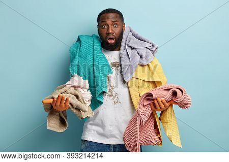 Isolated Shot Of Indignant Black Ethnic Man Has Bristle Overloaded With Laundry, Stares With Bugged