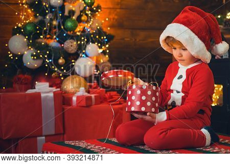 Lovely Baby Enjoy Christmas. Opening Gift. Santa Boy Little Child Celebrate Christmas At Home. Famil