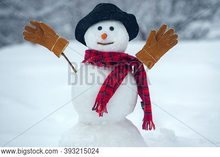 The Snowman Is Wearing A Fur Hat And Scarf. Happy New Year. Christmas Background With Snowman. Happy