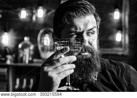 Hipster Barman With Martini Or Liquor. Bearded Man Wearing Suit And Drinking Alcohol. Drink And Cele