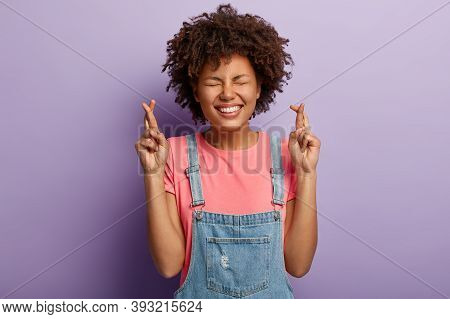 Charming Glad Woman Awaits Dream Come True, Crosses Fingers For Good Luck, Has Toothy Smile, Eyes Sh