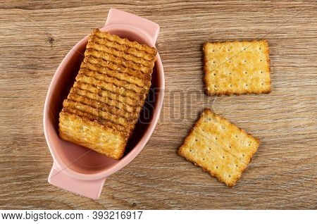Stack Of Crunchy Cookies With Sesame In Pink Bowl, Crackers On Wooden Table. Top View