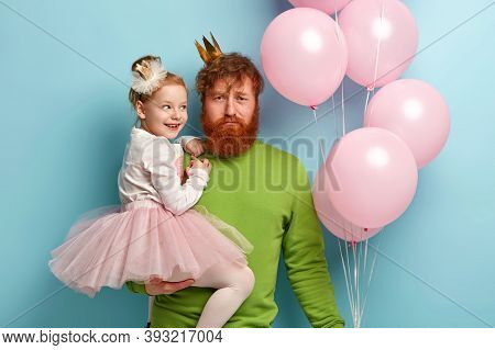 Candid Shot Of Redhead Father Holds On Hands Small Daughter Who Wears Crown, White Jumper And Tulle