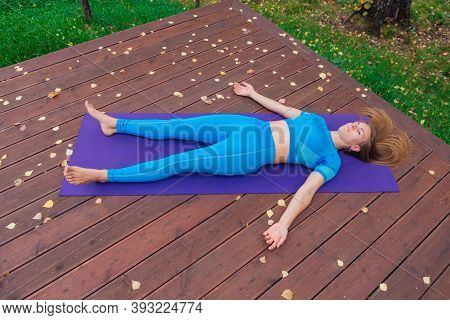 Young Woman Relaxing After Yoga Exercises In Autumn Park.