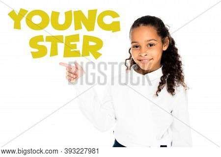 African American Schoolgirl Pointing With Finger At Youngster Lettering While Looking At Camera Isol