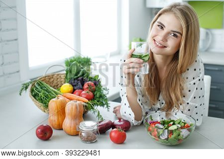 Young Woman Drinking Water Near The Table With Fruits And Vegetables In The Kitchen. Healthy Food, D