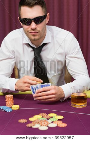 Man sitting at table in the casino wearing sun glasses