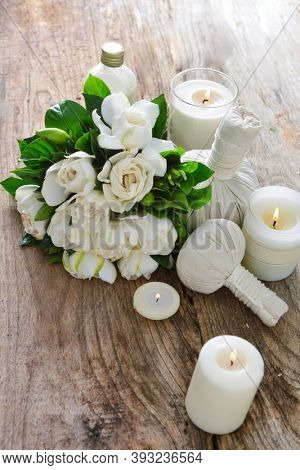 Spa setting with gardenia ,bottles of essential oil  , herbal ball, candle , herbal ,bal on wooden background