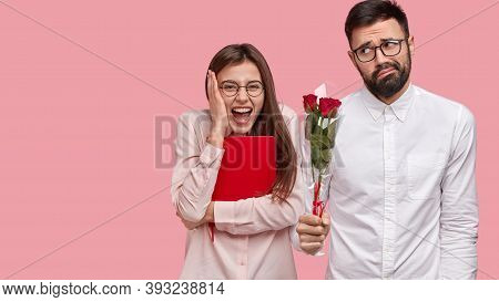 Overjoyed Glad Woman Has First Date, Expresses Positive Emotions, Awkward Guy Stands Near With Bouqu