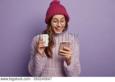 Laughing Joyful Woman Holds Smartphone, Smiles As Views Funny Photos On Smartphone, Feels Carefree,