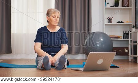 Old Woman Sitting On Yoga Mat Stretching Body Watching Exercise Lesson On Laptop. Retired Old Person