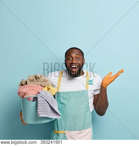 Vertical Shot Of Glad Smiling Man Gestures With Hesitation, Carries Basket With Laundry Towels, Does