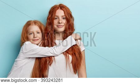 Two Adorable Foxy Girls Sisters Embrace Indoor, Look At Camera With Green Eyes. Pretty Freckled Litt
