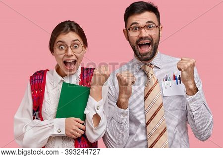 Overjoyed Clumsy Woman And Man Nerds Clench Fists, Celebrate Finishing Preparing For Seminar, Wear S