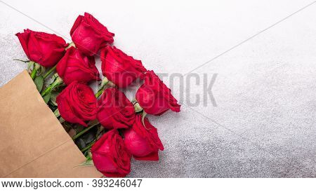 Craft Paper Shopping Bag With Flowers On Stone Background. Red Roses In A Brown Kraft Bag. Copy Spac