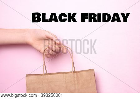 Female Hand Holds A Craft Bag For Shopping On A Bright Pink Background. Ecological Paper Shopping Ba