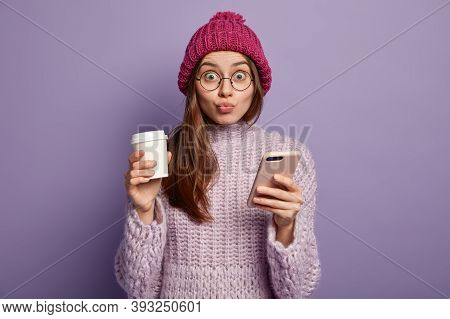 View Of Attractive Surprised Young Female Has Folded Lips, Uses Mobile Phone Application, Drinks Tak