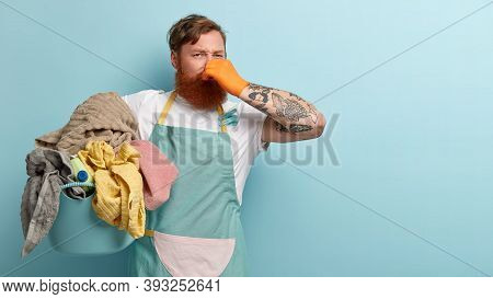 Foxy Bearded Man Covers Nose, Holds Pile Of Dity Laundry In Basin, Smells Unpleasant Stinch, Has Tat