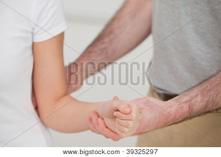 Close-up of a man examining the elbow of a woman in a room