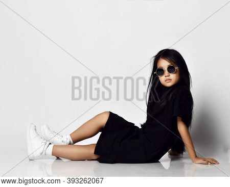 Cool Asian Kid Girl In Stylish Black Dress, Round Sunglasses And White Sneakers Sitting On Floor Sid