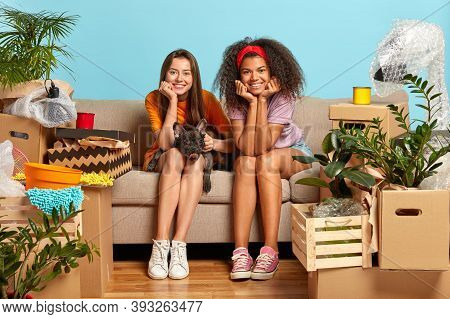 Photo Of Two Beautiful Diverse Female Students Change Place Of Living, Happy To Move In Modern Apart