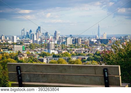 View Towards London City Skyline From Parliament Hill In Hampstead Heath Through An Empty Bench