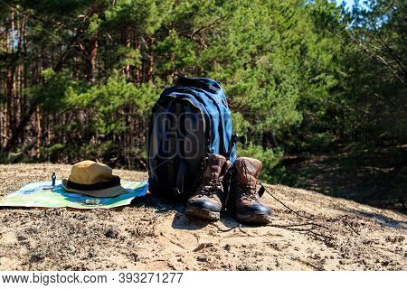 Tourist Backpack With Hiking Boots, Hat, Compass And Map On The Glade In Pine Forest. Trekking Hike
