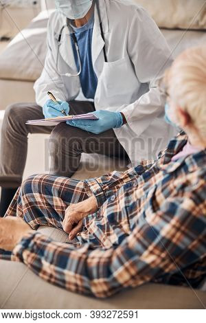 Geriatrician Taking Notes During The Medical Examination