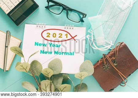 White Note With Word 2121 New Year New Normal With Stationary, Medical Masks And Hand Sanitizer On P