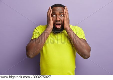 Shocked Terrified Black Bearded Man Looks In Terror, Keeps Both Hands On Head, Sees Something Horrif