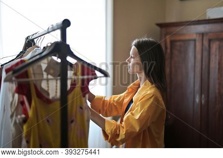 young woman chooses a dress in a hanger