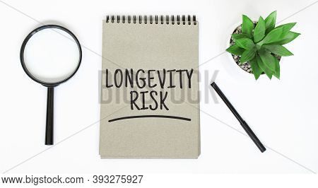 A Magnifying Glass, A Blank Brown Notebook On A White Table. Longevity Risk Sign
