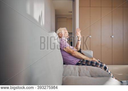 Joyous Caucasian Male Pensioner Waving At Someone