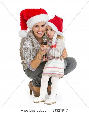 Christmas Portrait Of Happy Mother And Baby Girl Singing Into Mi