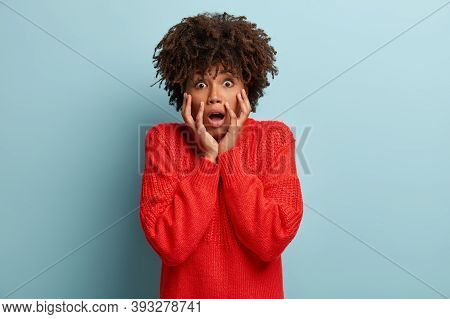 Stupefied Black Young Woman With Afro Hairstyle, Expresses Excitement And Thrill, Keeps Jaw Dropped,