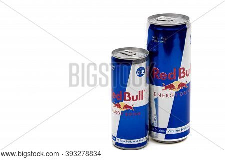 London, United Kingdom, 14th October 2020:- A Large And Small Can Of Red Bull Energy Drink Isolated
