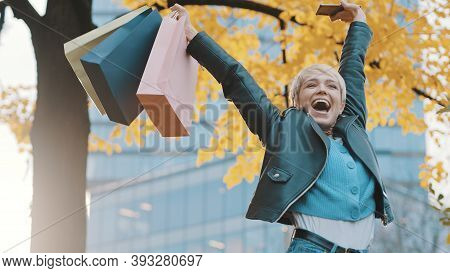 Happy Young Girl Jumping With The Shopping Bags. Sales And Discounts Concept. High Quality Photo