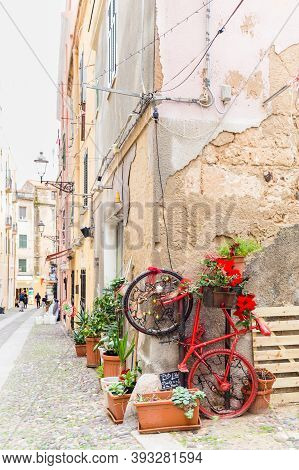 Alghero, Sardinia Island, Italy - December 28, 2019: Colorful Red Bike With Flowers In The Street Of