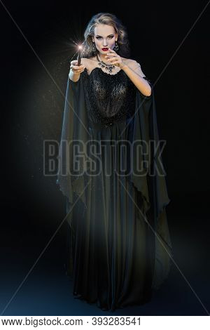 Full length portrait of a enchanting young witch with a magic wand conjuring surrounded by magic lights. Halloween magic. Celebration, party.